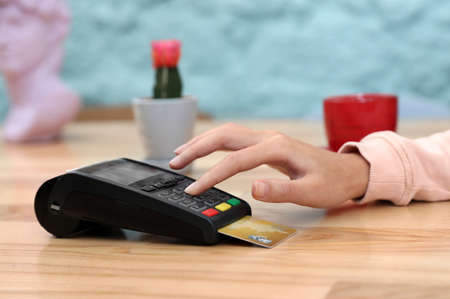 Woman using card machine for non cash payment at table, closeup Imagens