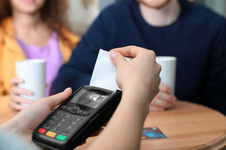Clients using credit card machine for non cash payment in cafe, closeup Imagens