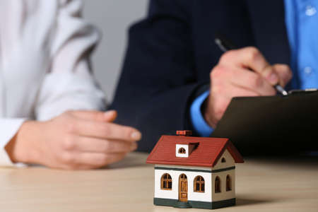 House model and real estate agent working with client at table, closeup. Home insurance Reklamní fotografie