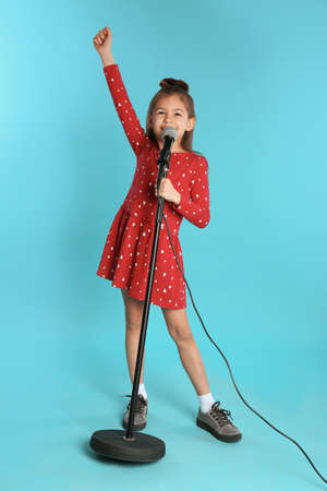 Cute funny girl with microphone on color background