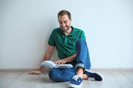 壁の近くの床に本を読む若い男 写真素材