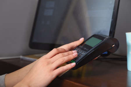 Woman using credit card machine for non cash payment in cafe, closeup. Space for text