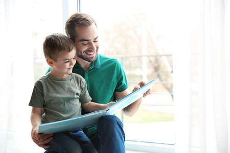 Young man and his little son reading book near window at home