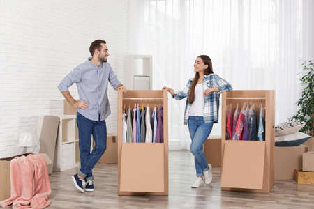 Young couple near wardrobe boxes at home Stock Photo - 121429622
