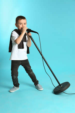 Cute funny boy with microphone on color background