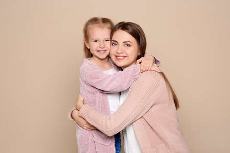 Retrato de mujer joven y su hija sobre fondo de color