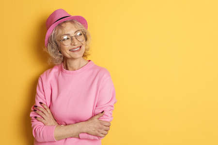 Portrait of mature woman in hipster outfit on color background. Space for text Imagens
