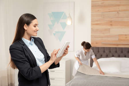 Housekeeping manager checking maid work in hotel room