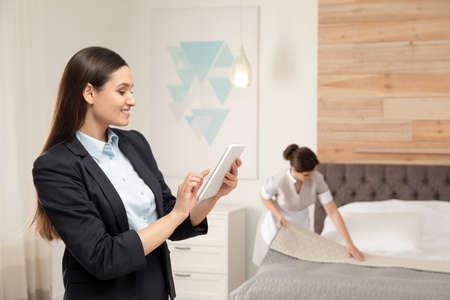 Responsable de l'entretien ménager vérifiant le travail de la femme de chambre dans la chambre d'hôtel