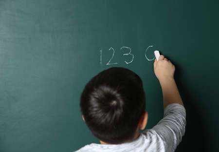 Child writing math sum on chalkboard. Space for text 스톡 콘텐츠