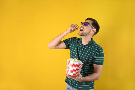 Man with 3D glasses eating tasty popcorn on color background. Space for text