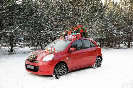 Car with Christmas tree, wreath and gifts in snowy forest on winter day
