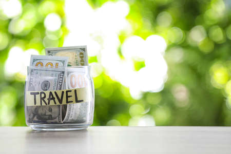 Glass jar with money and label TRAVEL on table against blurred background. Space for text