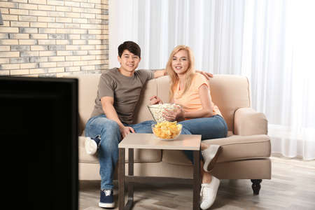 Young couple with snacks watching TV on sofa at home