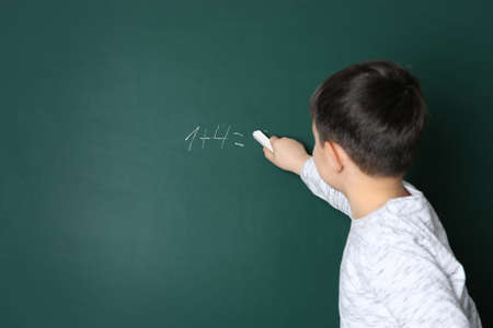 Child writing math sum on chalkboard. Space for text 写真素材