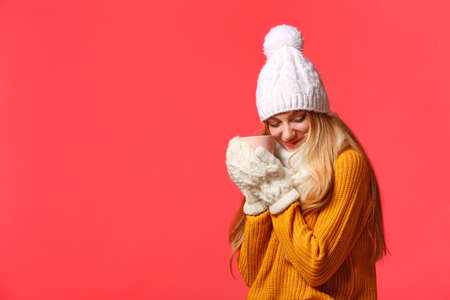 Portrait of emotional young woman in stylish clothes with cup on color background, space for text. Winter atmosphere