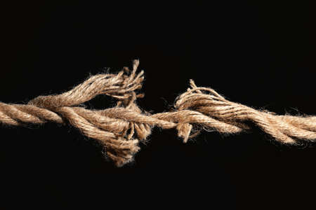 Rupture of cotton rope on black background Stock Photo