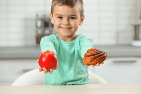 Little boy with pastry and apple at home. Diabetes diet Reklamní fotografie