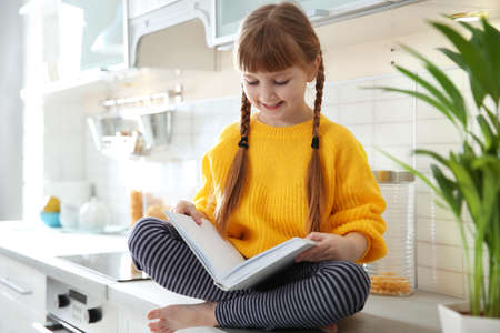 Cute little girl reading book in kitchen at home