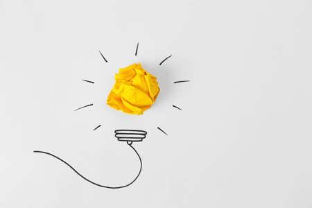 Composizione con palla di carta stropicciata, disegno della lampadina e spazio per il testo su sfondo bianco, vista dall'alto. Concetto creativo