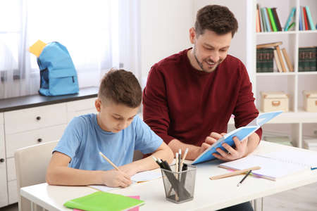 Dad helping his son with homework in room Banco de Imagens