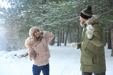 Happy couple playing snowballs in winter forest