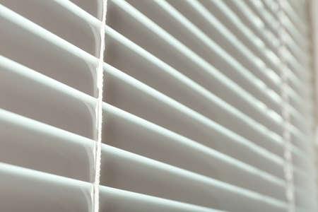 Closed modern white window blinds, closeup view