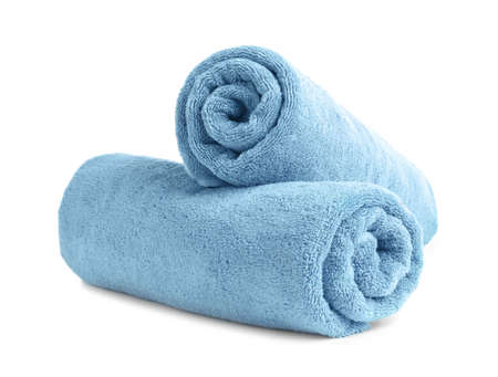 Asciugamani in morbida spugna arrotolati su sfondo bianco