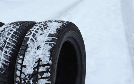 New winter tires on fresh snow, closeup. Space for text