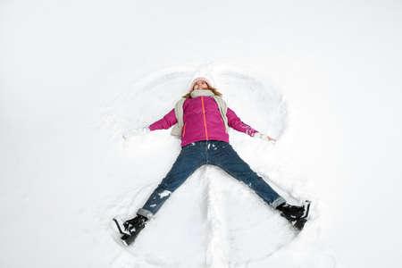 Beautiful woman making snow angel on winter day Imagens