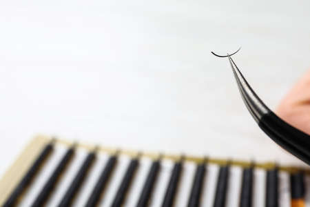Tweezers with artificial eyelash on blurred background, closeup. Space for text 免版税图像