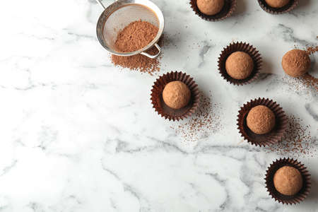 Flat lay composition with tasty raw chocolate truffles on marble background, space for text