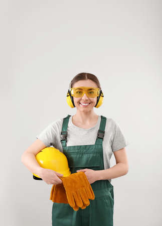 Female industrial worker in uniform on light background. Safety equipment Imagens