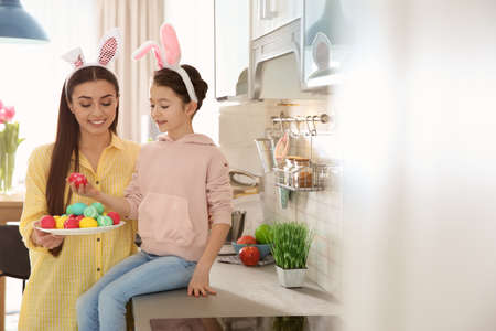 Mother and daughter with bunny ears headbands and painted Easter eggs in kitchen, space for text 版權商用圖片
