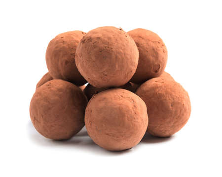 Delicious raw chocolate truffles on white background