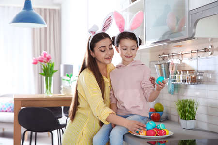 Mother and daughter with bunny ears headbands and painted Easter eggs in kitchen