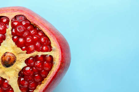 Ripe red pomegranate fruit with juicy seeds on color background, top view. Space for text Stock Photo