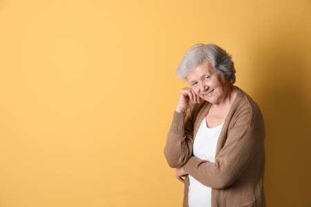 Portrait of grandmother in stylish clothes on color background, space for text