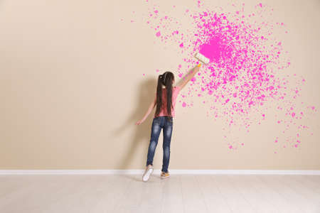 Child painting with roller brush on color wall, space for text