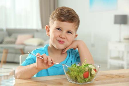 Adorable niño comiendo ensalada de verduras en la mesa en la habitación Foto de archivo