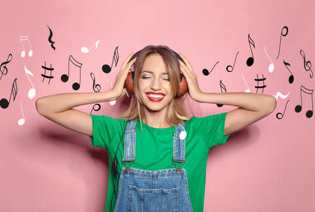 Young stylish woman listening to music with headphones and flying notes against color background