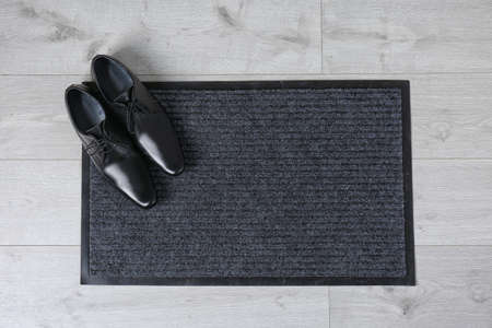Door mat and shoes on floor, top view. Space for text