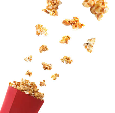 Delicious caramel popcorn falling into carton cup on white background