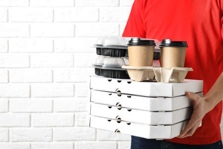 Courier with stack of orders near white brick wall, space for text. Food delivery service