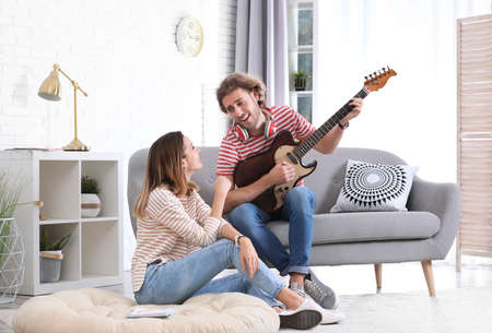 Young man playing electric guitar for his girlfriend in living room