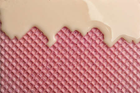 Hot white chocolate on wafer, closeup. Crispy food