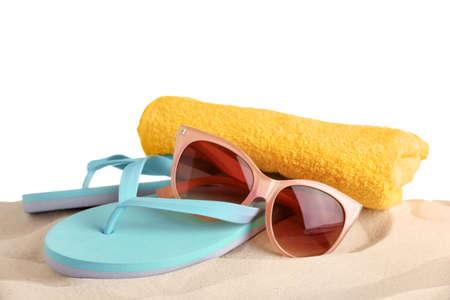 Accesorios de playa sobre arena contra el fondo blanco.