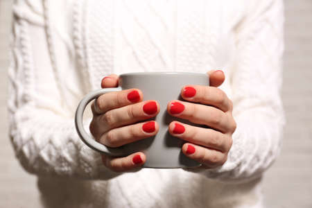Woman with red manicure holding cup, closeup. Nail polish trends
