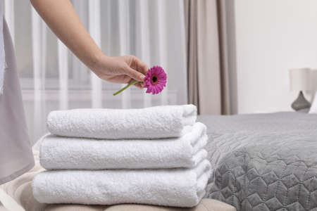 Maid putting flower on fresh towels in hotel room, closeup Stock Photo