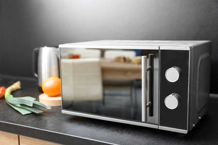 Modern microwave oven and ingredients on table in kitchen Фото со стока